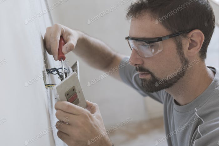 Professional electrician, installing sockets at home