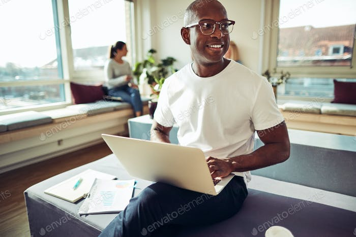 Smiling African businessman working online at his office desk
