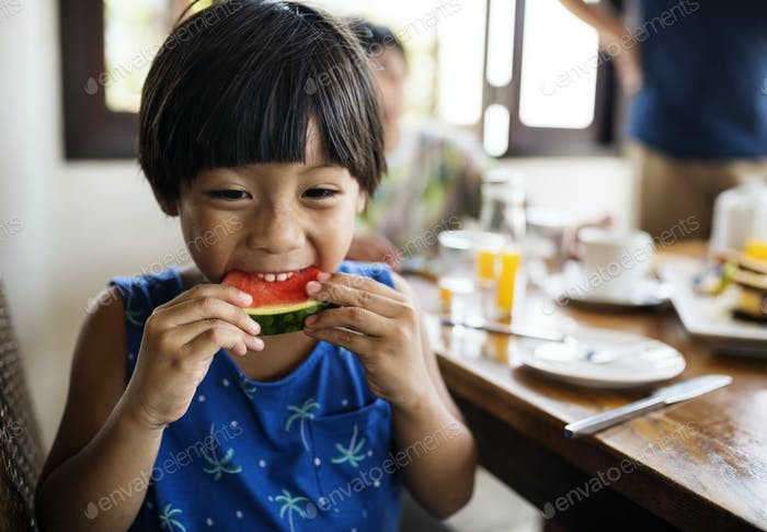 Asian boy snacking on a watermelon