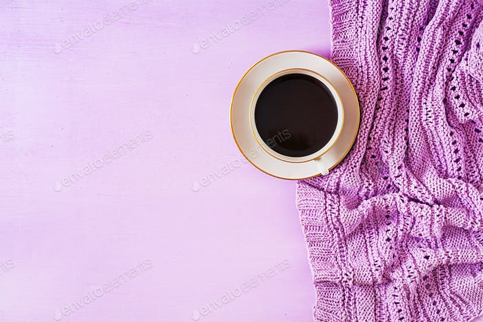 Cup of hot coffee on violet table, close up photo knitted sweater with mug
