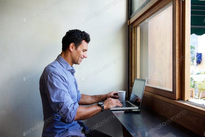 Modern business man sitting at cafe with laptop