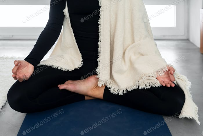 Anonymous woman in activewear and shawl meditating at home