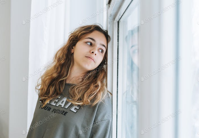Beautiful teenager girl with curly hair sitting on window sill