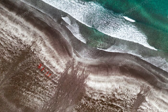 Aerial view of black sand beach and ocean waves