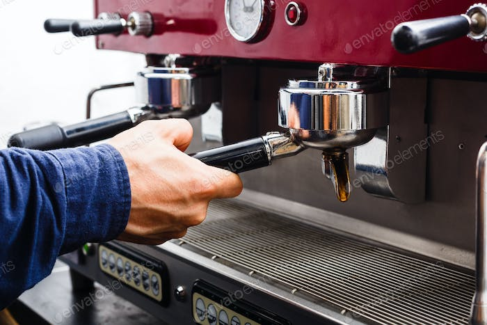 Closeup of barmen hand brewing espresso in professional coffee machine