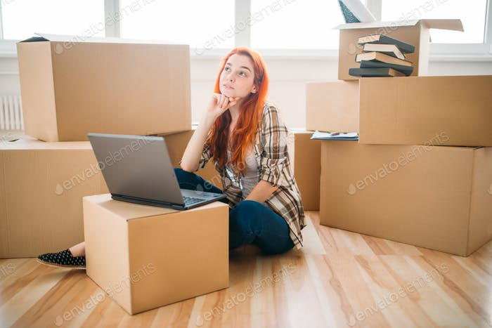 Girl using laptop among cardboard boxes, new house