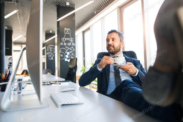 Geschäftsmann trinken Kaffee mit Beinen auf dem Schreibtisch.