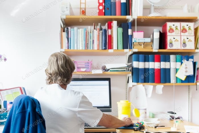 Doctor looking at computer screen in examination room