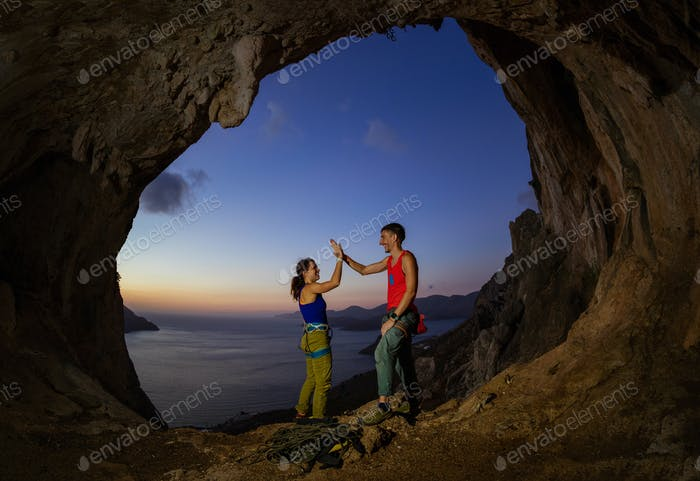 Couple of rock climbers giving high five and cheering