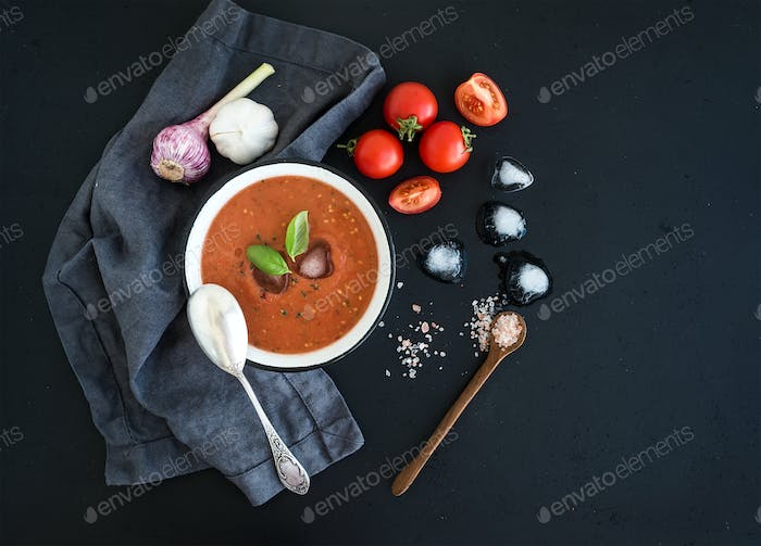 Gazpacho soup in rustic metal bowl with fresh tomatoes, ice cubes, garlic and basil