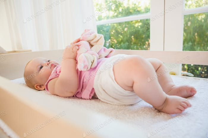 Beautiful cute baby girl in her crib at home in bedroom