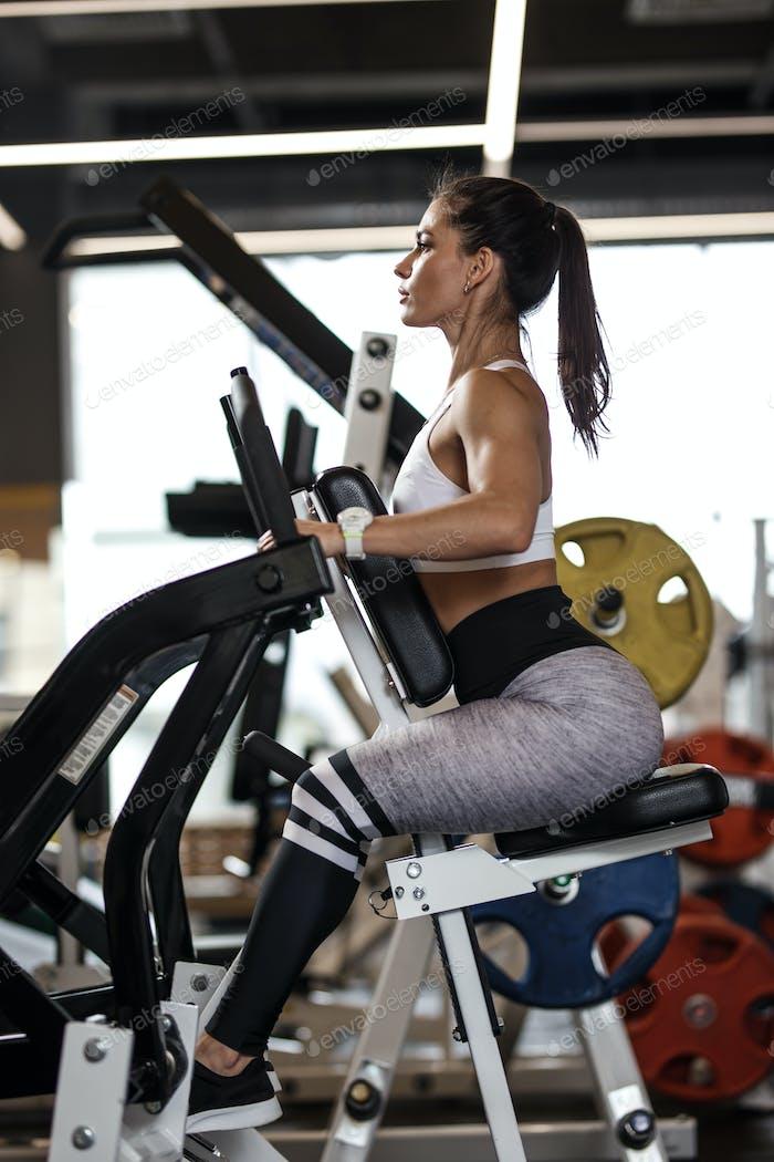 Junge sportliche Mädchen gekleidet in Sportbekleidung tun Übungen mit speziellen Sportgeräten in der modernen