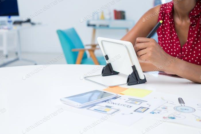 Female graphic designer using graphic tablet at desk
