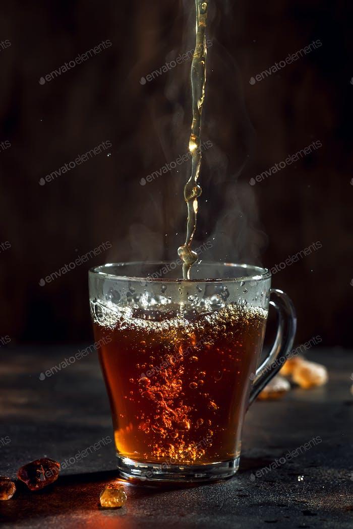 Schwarzer Tee Gießen in Glasbecher mit natürlichem Dampf