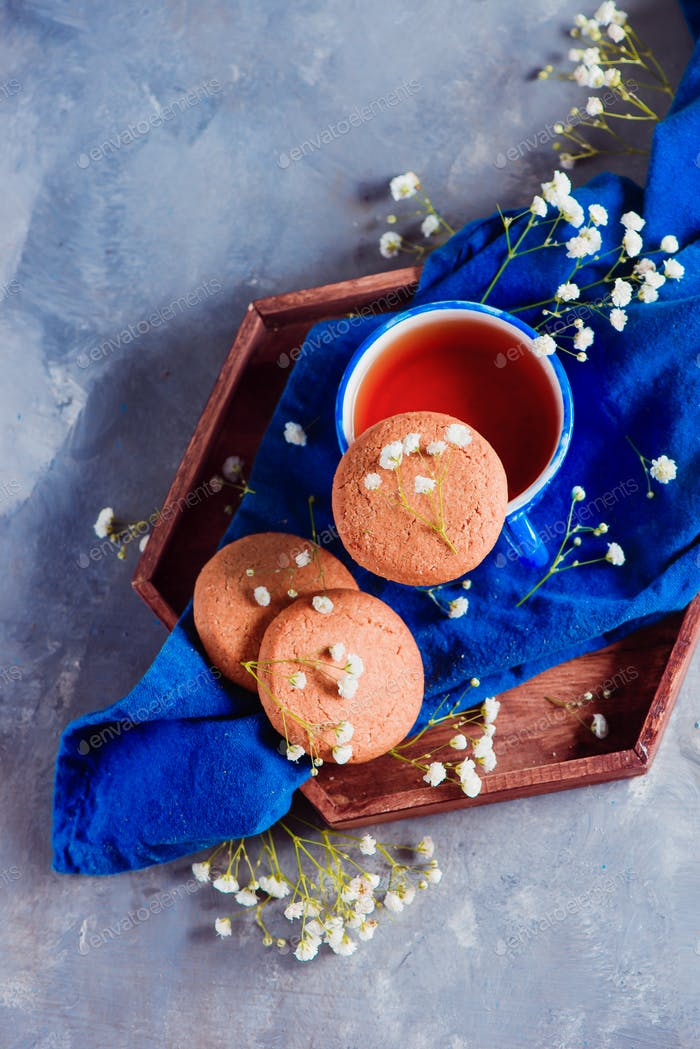 Oatmeal cookies, a small blue teacup and linen napkin on a wooden tray. Breakfast concept with
