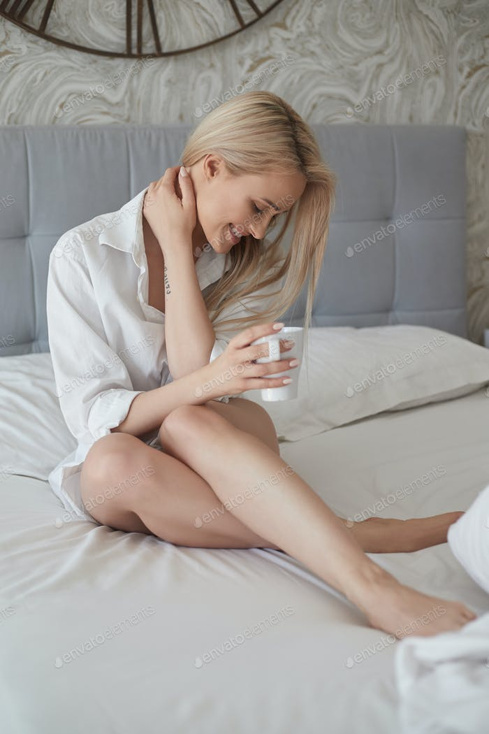 Beautiful blond woman drinking a coffee while sitting on her bed at home