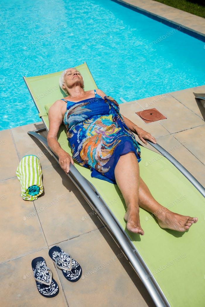 Senior woman sleeping on lounge chair
