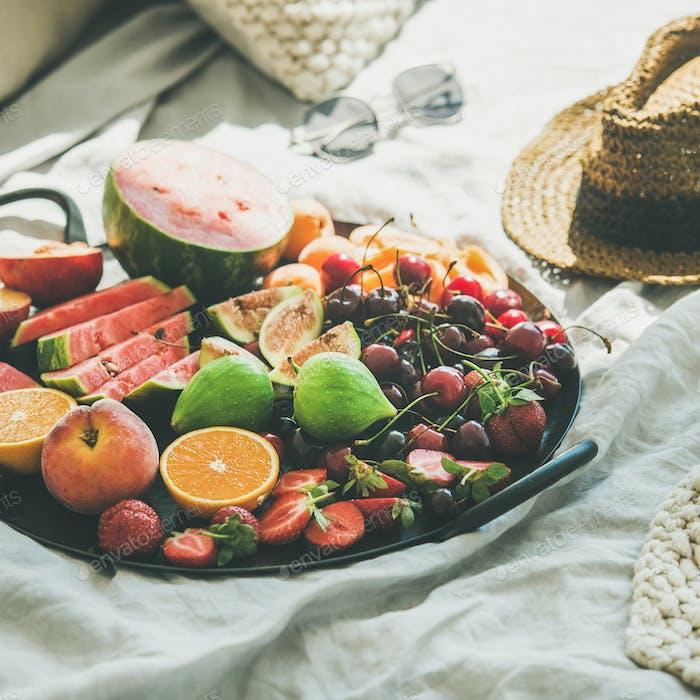 Bandeja llena de fruta sobre Fondo de manta ligera, cultivo cuadrado