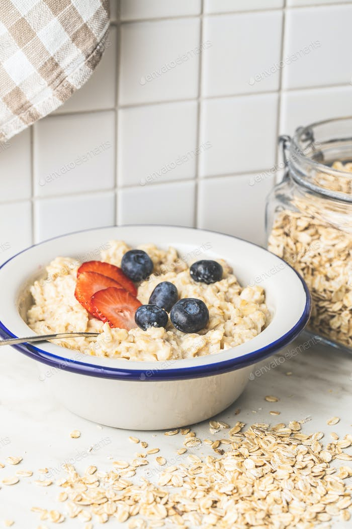 Bowl of oatmeal porridge with strawberries and blueberries.