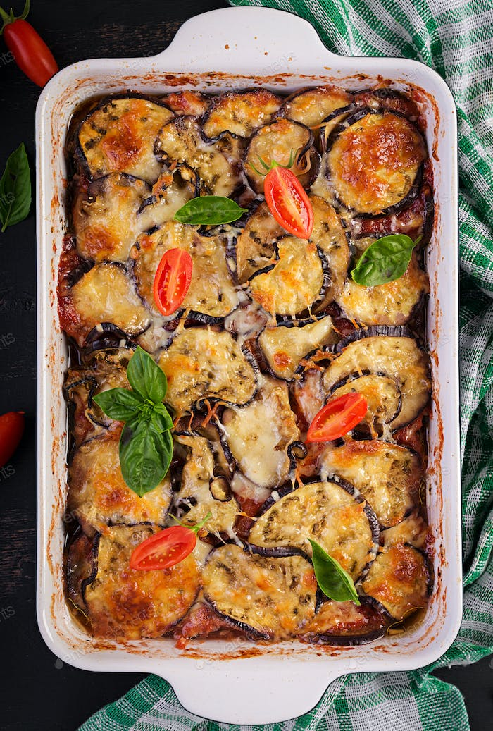 Baked eggplant with cheese on a dark wooden table. Parmigiana melanzane. Top view. Italian cuisine.