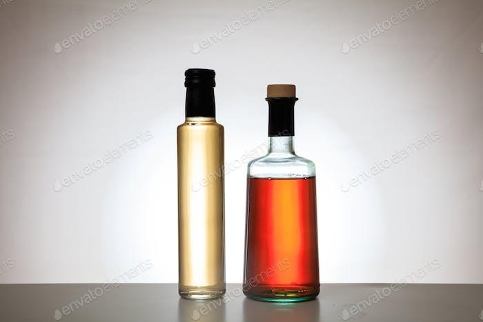 Bottles of vinegar on gradient background
