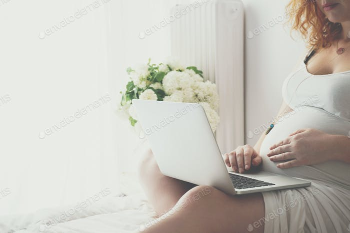 Young pregnant woman relaxing on bed with a laptop
