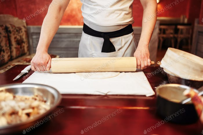 Male chef roll out the dough with a rolling pin