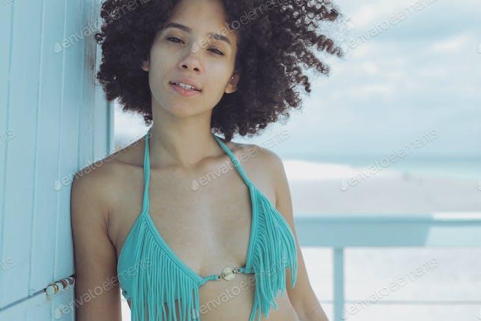 Charming black model in bikini on beach