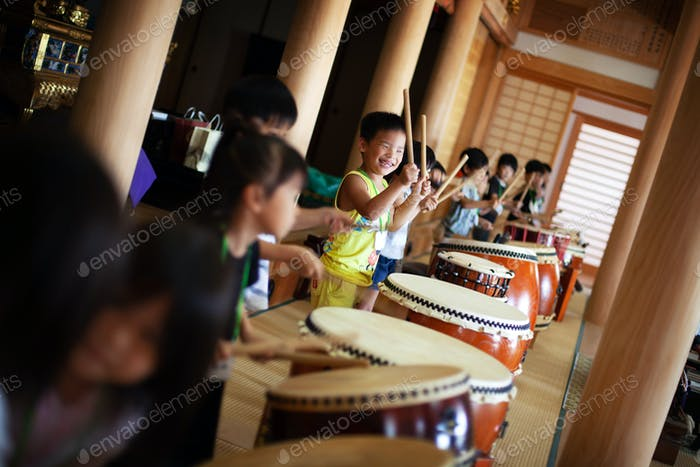 Group of children playing the drums in a temple, a traditional set of drums.