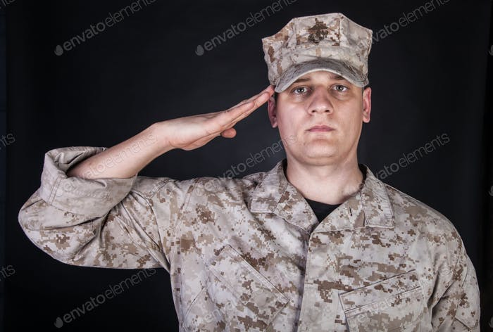 Portrait of marine saluting and looking at camera