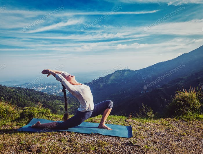 Sporty fit woman practices yoga Anjaneyasana in mountains