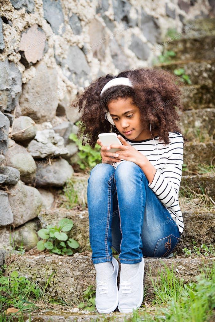Красивая афро-американская девушка со смартфоном и наушниками.