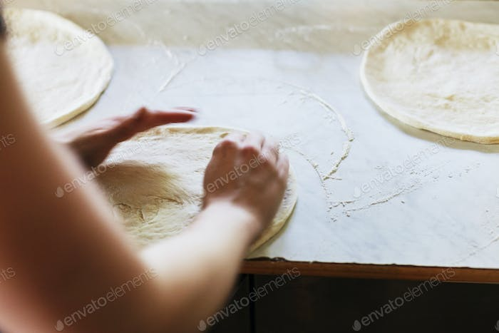Woman flattening pizza base on counter at restaurant kitchen