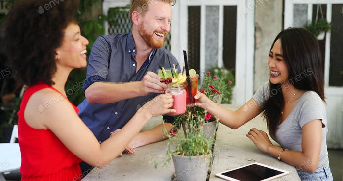 Diverse group of happy friends having fun, talking in cafe outdoor at summer