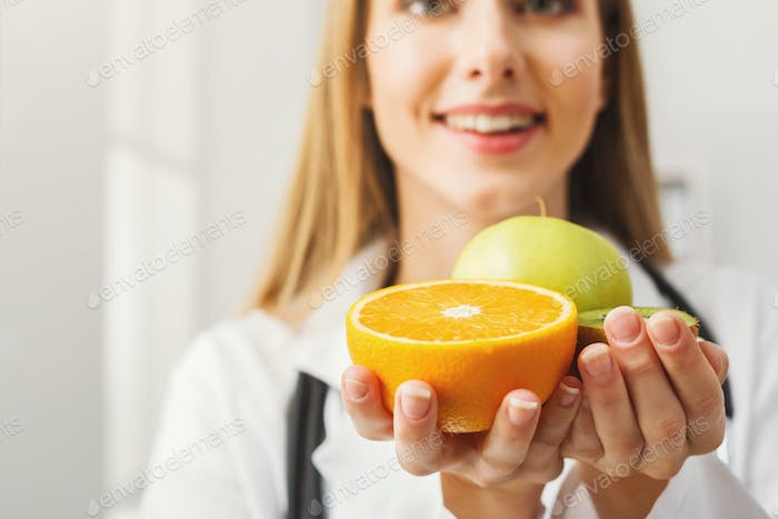 Smiling nutritionist woman with fruit at office
