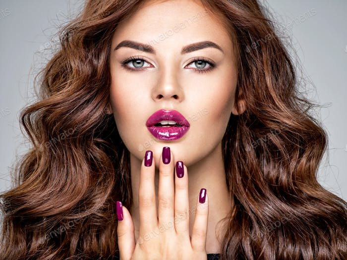 Beautiful and stunning woman with  purple lipstick on lips and fingernails.