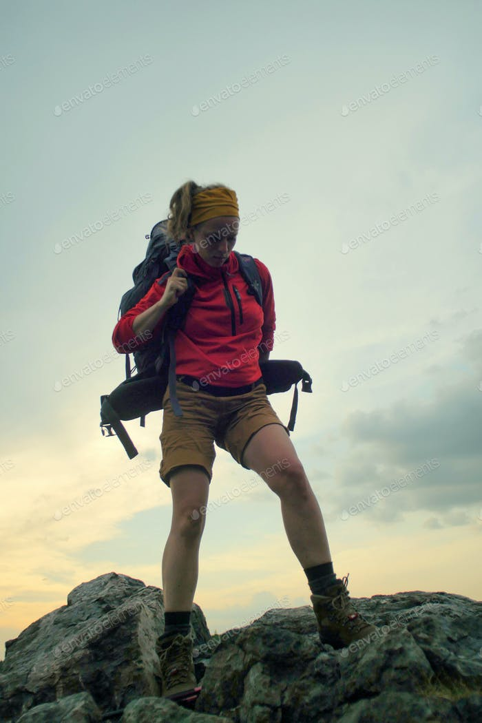 hiker putting on a backpack