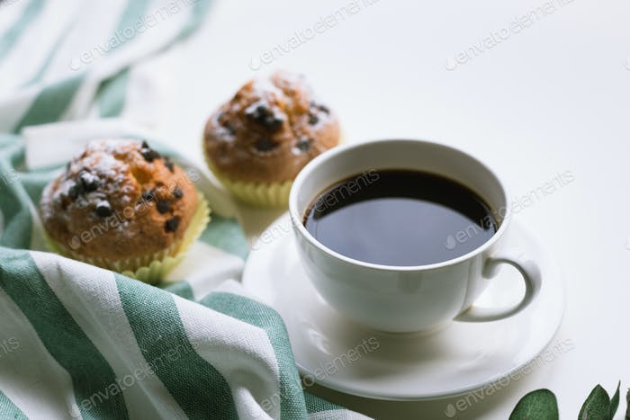 Coffee and two muffins on white background