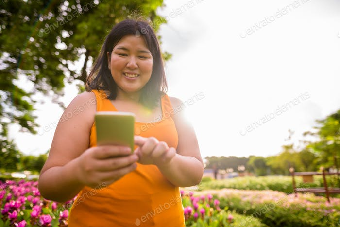 Beautiful happy overweight Asian woman using phone in park