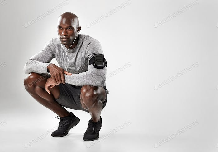 Young african man crouching on grey background
