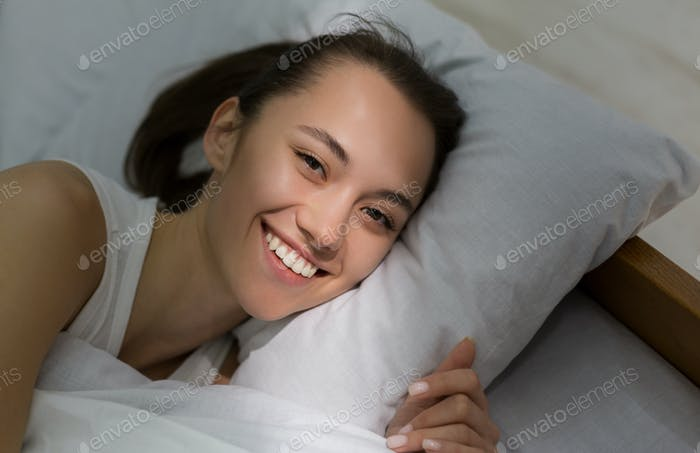 Happy woman waking up with sunbeam on her face