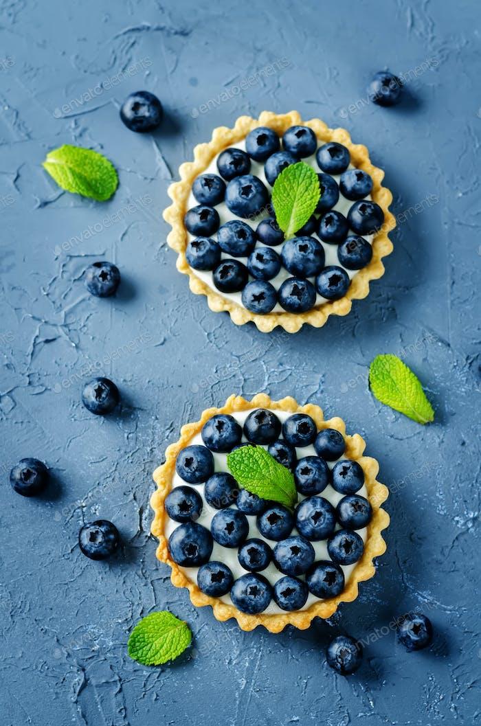Blaubeer-Törtchen mit frischen Beeren und Minzblättern