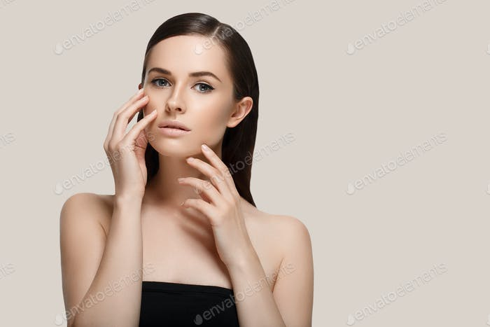 Beautiful woman face close up hand touching face  studio on gray background
