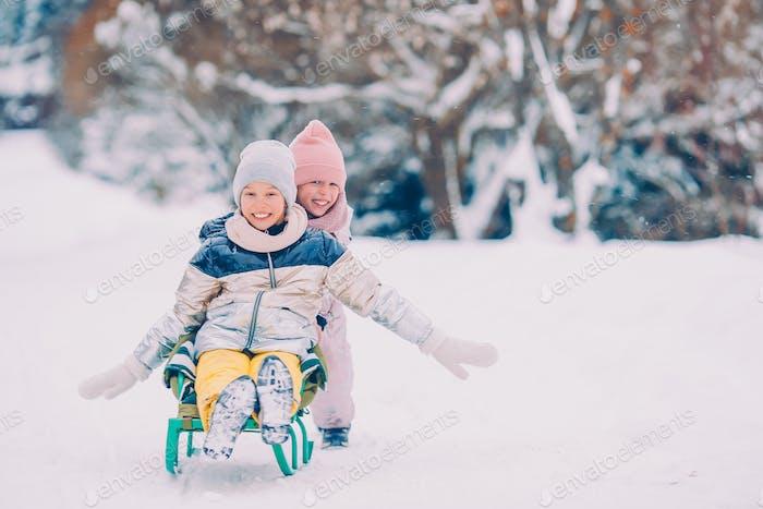 Adorable little happy girls sledding in winter snowy day