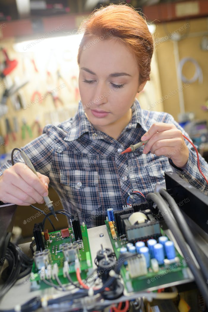 Female technician using probe in electrical system
