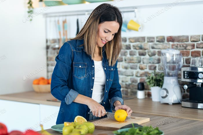 Pretty young woman cutting lemons for preparing detox beverage in the kitchen at home.
