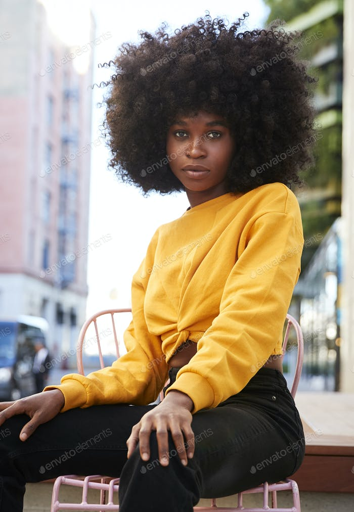 Young black woman with afro hair and sitting on a chair in the street looking to camera, vertical