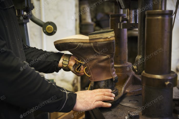 Close up of worker in a shoemaker's workshop, using a machine to make a leather ankle boot.