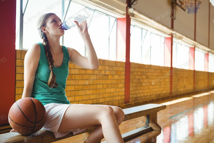 Woman drinking water while sitting on bench