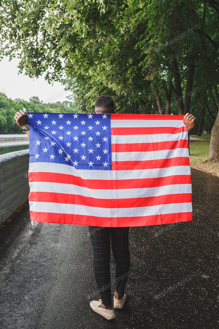Black african-american man holding USA flag from his back walking outdoors